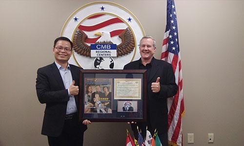 美成达小邱总(邱少波先生)接受CMB总裁Patrick F.Hogan先生赠送带有陈先生一家采访照片的杂志以及颁发给美成达的荣誉证书